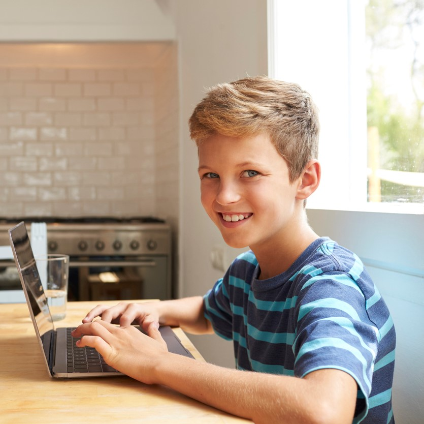 Portrait Of Boy At Home Using Laptop On Kitchen Table