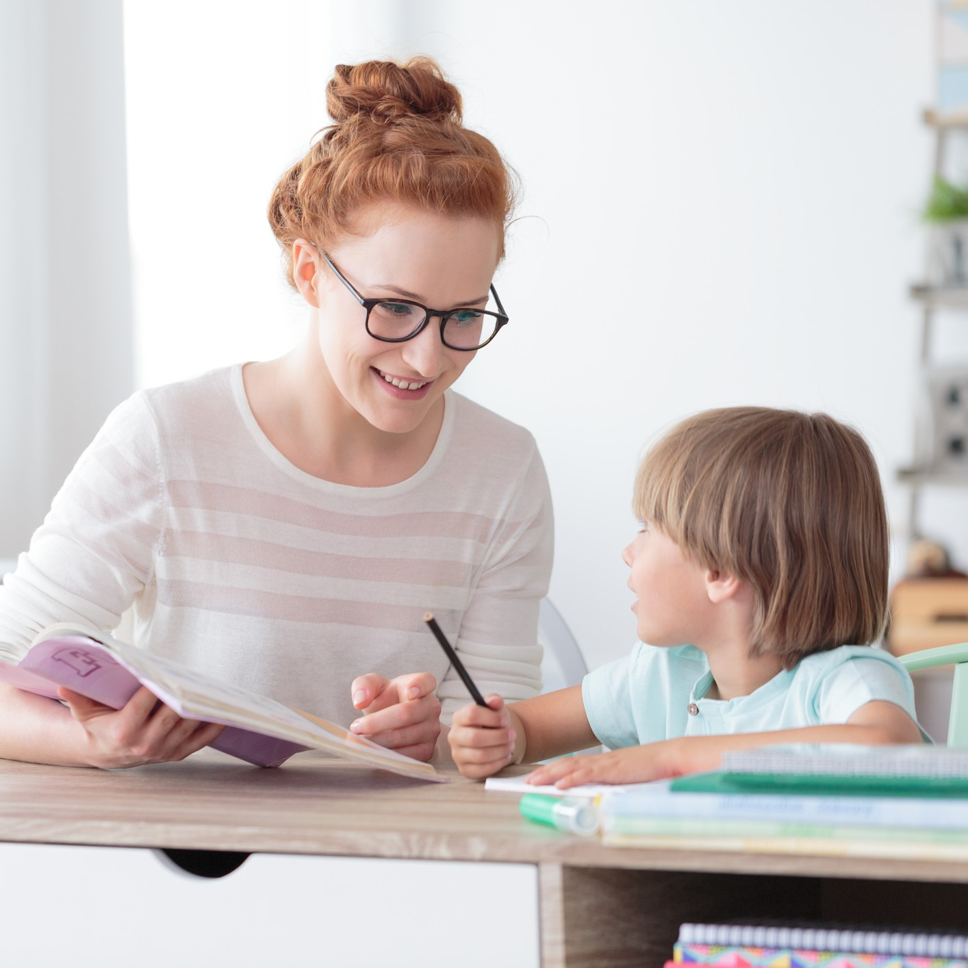 Smiling mother helping son with homework while sitting at desk with notebooks in home office