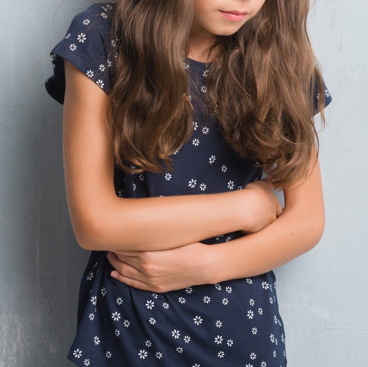 Young girl with hands on stomach because indigestion, painful illness feeling unwell.